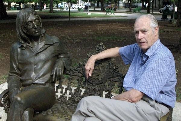 """2002年,马丁坐在哈瓦那一座公园的列侬塑像旁边。从1962年到1970年,马丁为""""披头士""""制作了13张专辑与22首单曲,这些作品总长不到10小时,但为流行音乐的世界带来了革命。(Rafael Perez/Reuters)"""